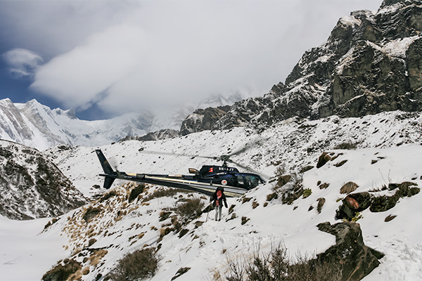 Things You Should Know About Travel Insurance: Helicopter landing ahead of me approaching Machhapuchhare Base Camp, Nepal