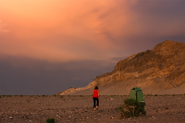 A lone figure walks to the toilet tent through rocky ground beneath a fiery sky
