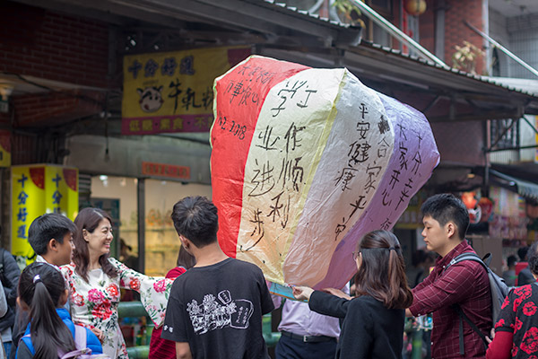 Day Trip From Taipei: A family getting ready to release their sky lantern on the railway tracks at Shifen Old Street, Taiwan