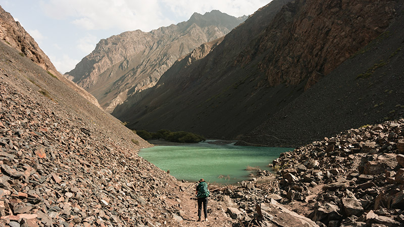 A female hiker with a backpack standing in front of a bright green lake surrounded by mountains in the Jizeu Valley
