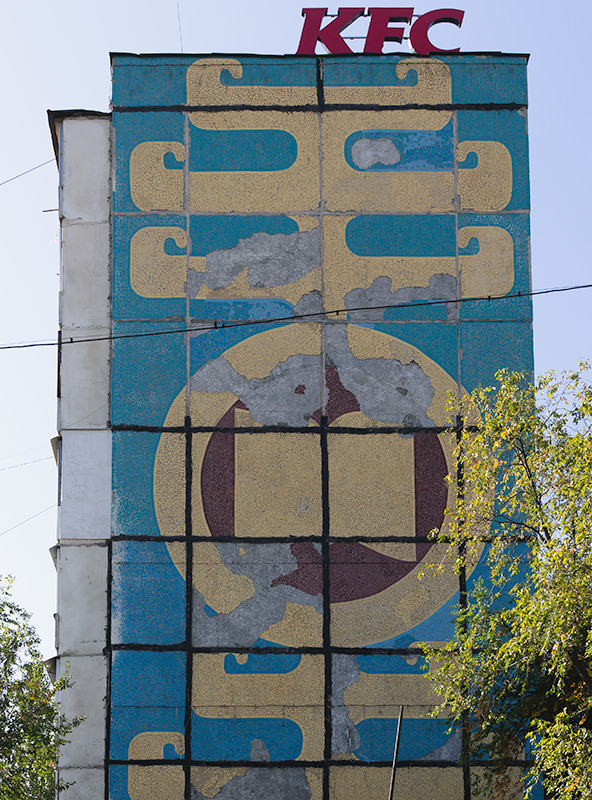 A huge decorative pattern of blue and yellow Kyrgyz motifs emblazoned on the side of a multi-story block in Bishkek