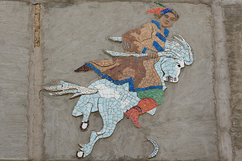 A mosaic of a man dressed in Kyrgyz attire riding a white horse on the side of a building in the 5th micro district of Bishkek