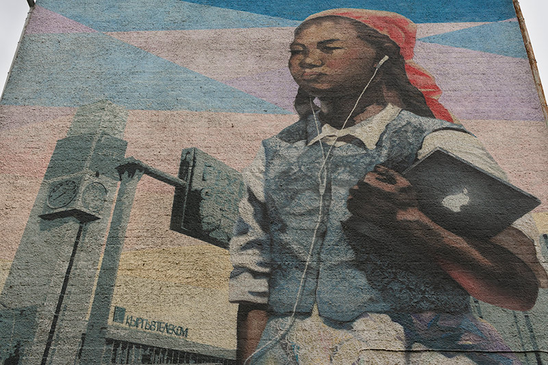 A modern mural of Semyon Chuikov's famous painting 'Daughter of Soviet Kirghizia' on a Bishkek building. The girl is holding an iPad and has white headphones in her ears.