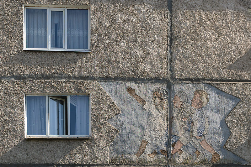 A sgraffito image of three children marching forth on the side of an apartment building in the 5th micro district of Bishkek