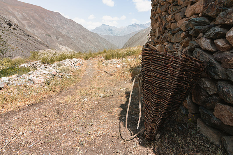 A traditional wicker basket for carrying things on your back sits against a stone wall in Jizeu Village