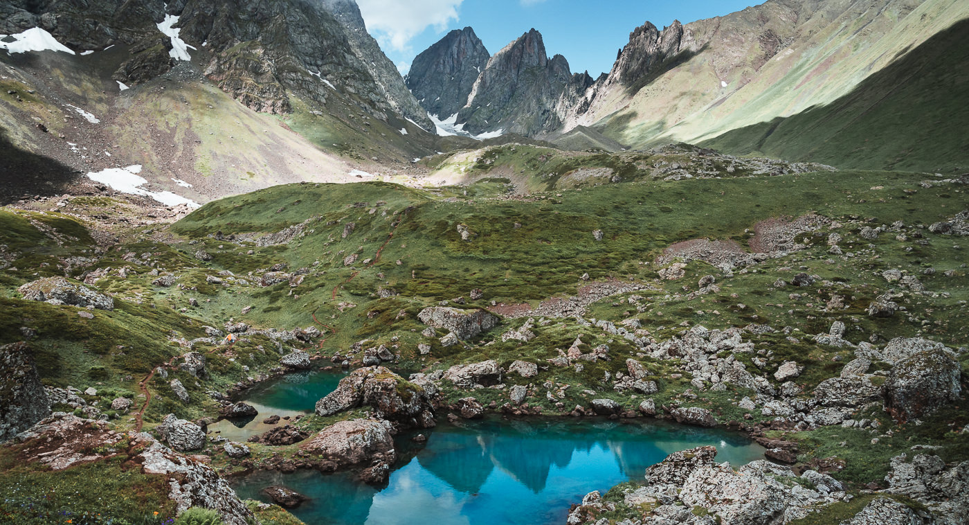The jagged peaks of Chaukhi Massif rising behind and reflected in the bold blue surface of Blue Abudelauri Lake