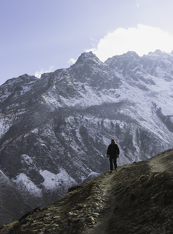 A person doing a short acclimatisation hike above Dharamsala on the Manaslu Cicuit, with a wall of snow covered mountains behind