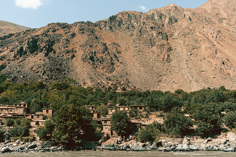 A village of mudbrick houses surrounded by trees on the Afghan side of the Panj River, mountains of the same colour as the houses rising behind, seen on a Pamir Highway Road Trip