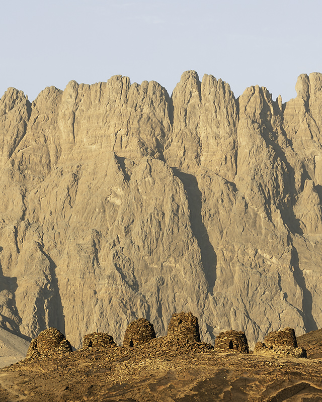 Beehive tombs in front of towering mountain Jebel Misht