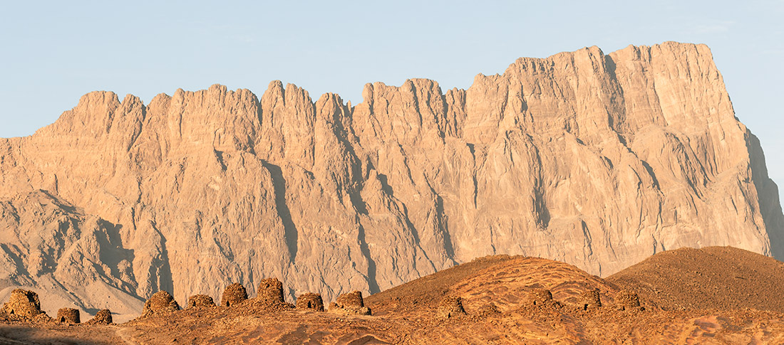 The Bronze Age beehive tombs at Al Ayn in Oman, glowing at golden hour with the distinctive shape of the mountain Jebel Misht rising behind
