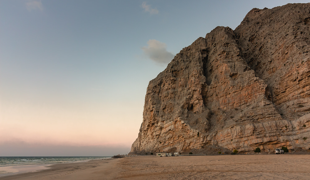 Al Jadi Beach in Musandam at sunset, sheer limestone cliffs rising behind the beach and coastal road