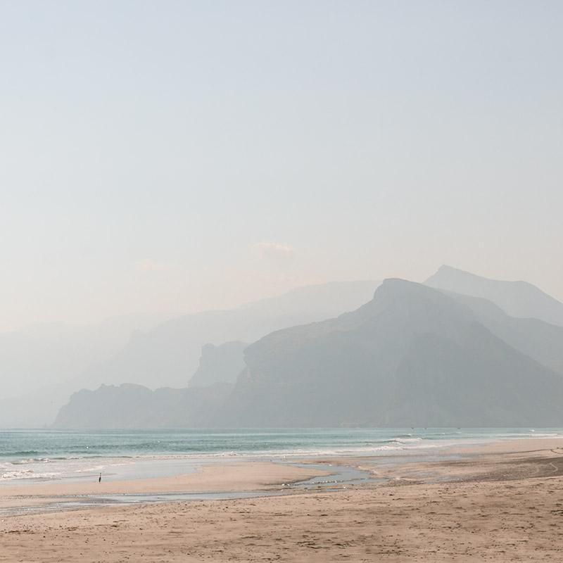 Hazy sunshine on Mugsayl Beach near Salalah with mountains in the background