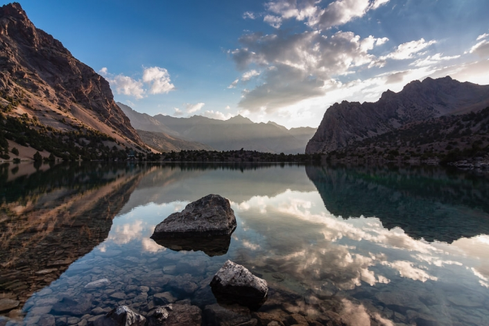 Sunrise reflections on the mirror-like surface of Alauddin Lake in the Fann Mountains of Tajikistan.