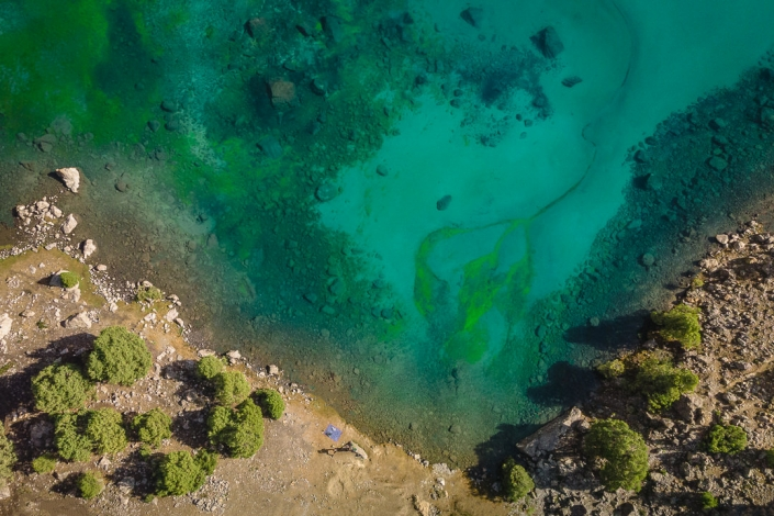 A top down view of the south shore of Alauddin Lake in Tajikistan's Fann Mountains, the water appearing a strange green colour from above..