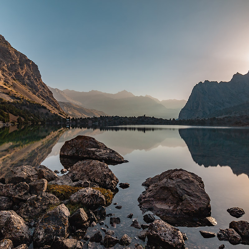 Sunrise over the perfectly still mirrored surface of Alauddin Lake in the Fann Mountains of Tajikistan