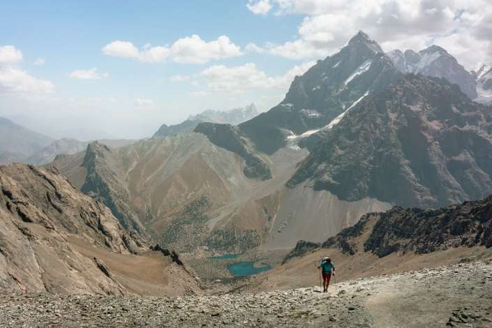 The view from the 3800 metre Alauddin Pass in the Fann Mountains in Tajikistan. A lone hiker reaches the pass, dwarfed by the sharp mountains. Below, the green blue Alauddin lakes look small but still catch the eye.