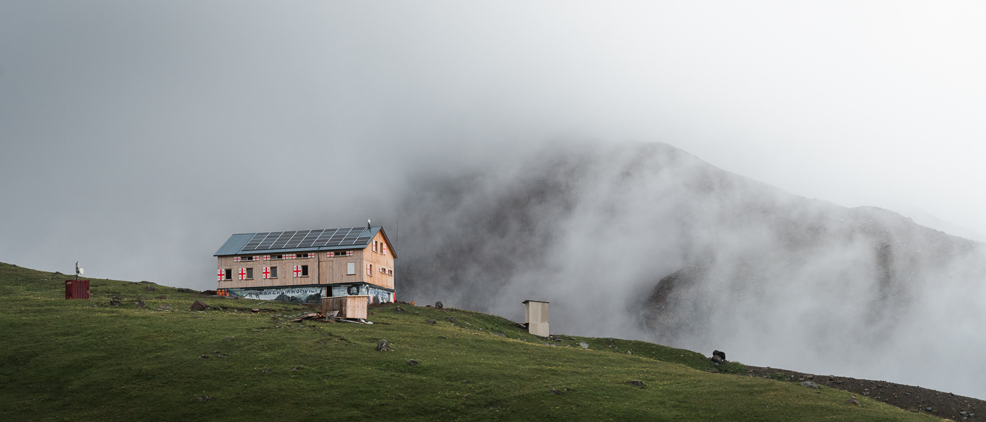 Altihut, a new and well appointed mountain hut, appears through the mist while hiking to Gergeti Glacier in Georgia