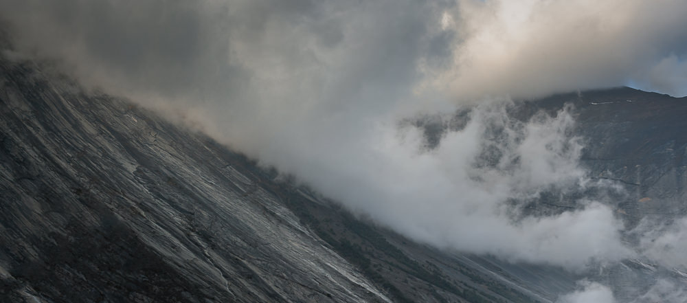 Clouds swirl around a sweeping concave mountainside at Dhukur Pokhari on the Annapurna Circuit Trek