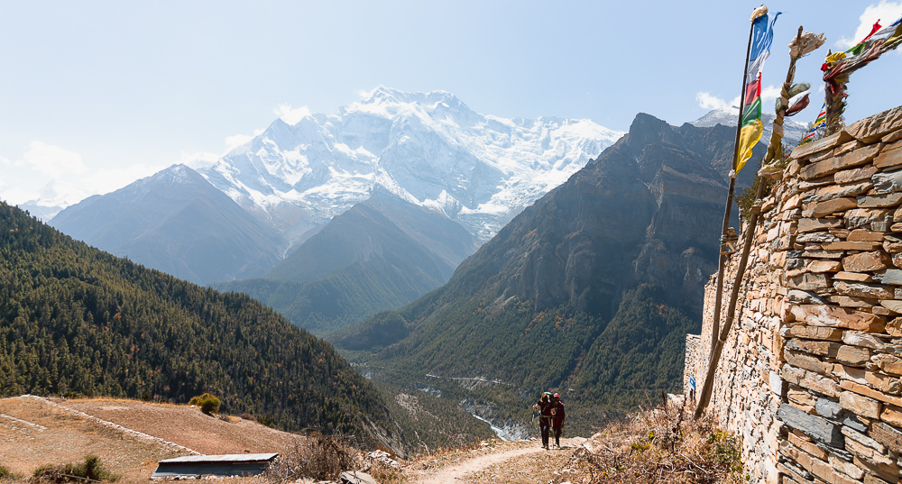 Two trekkers reaching Ghyaru (3700 m) at the end of a long climb from the valley below, with Annapurna II marking the skyline behind