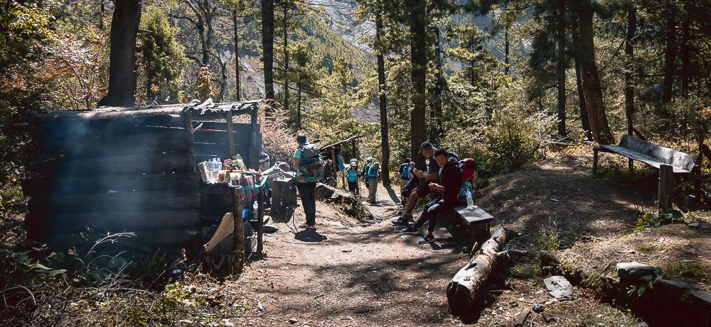 Trekkers rest at a makeshift refreshment hut on the forest trail up towards Dhukur Pokhari on the Annapurna Circuit trek