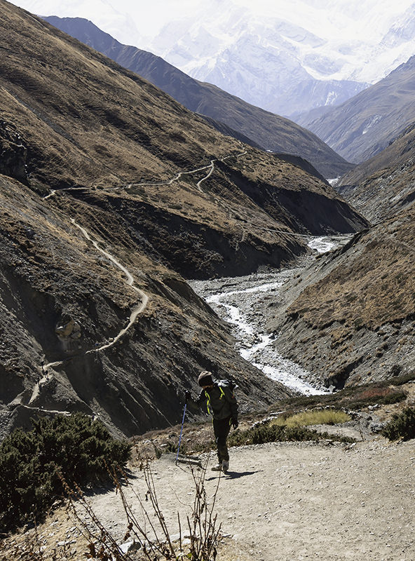 A trekker climbing up from the river, the trail and snowy mountains stretched out far into the distance behind him