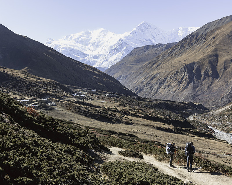 Two trekkers taking a break and looking down the valley towards snowy mountain peaks on the Annapurna Circuit trek