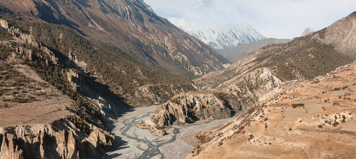 A glacier blue river snaking through the valley below the trail from Manang to Yak Kharka on the Annapurna Circuit Trek
