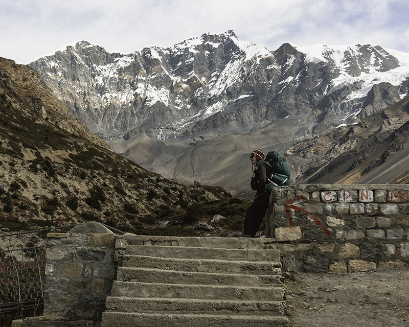 A trekker resting at the end of a suspension bridge in front of mountain views on the Annapurna Circuit