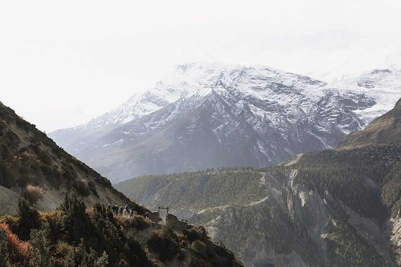 Trekkers turning north through a stone gate on the Annapurna Circuit trail, heading up into the mountains