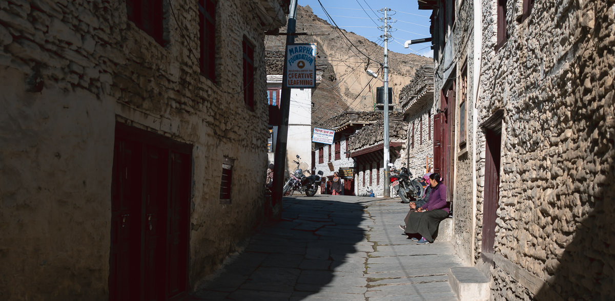 A street scene from Marpha, complete with motorbikes and whitewashed houses