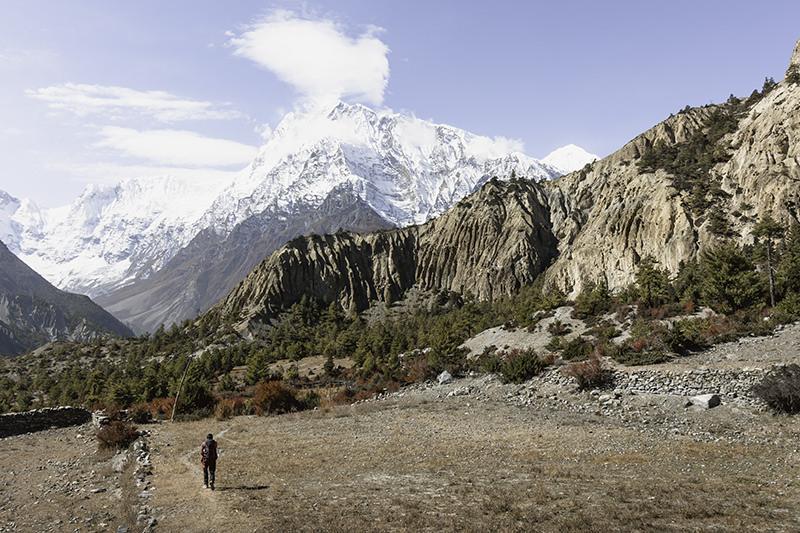 A trekker walking towards Cappadocia-esque rock formations on the way to Manang