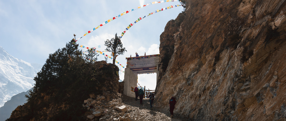 Trekkers approaching a large stone gate beneath prayer flags on the Annapurna Circuit