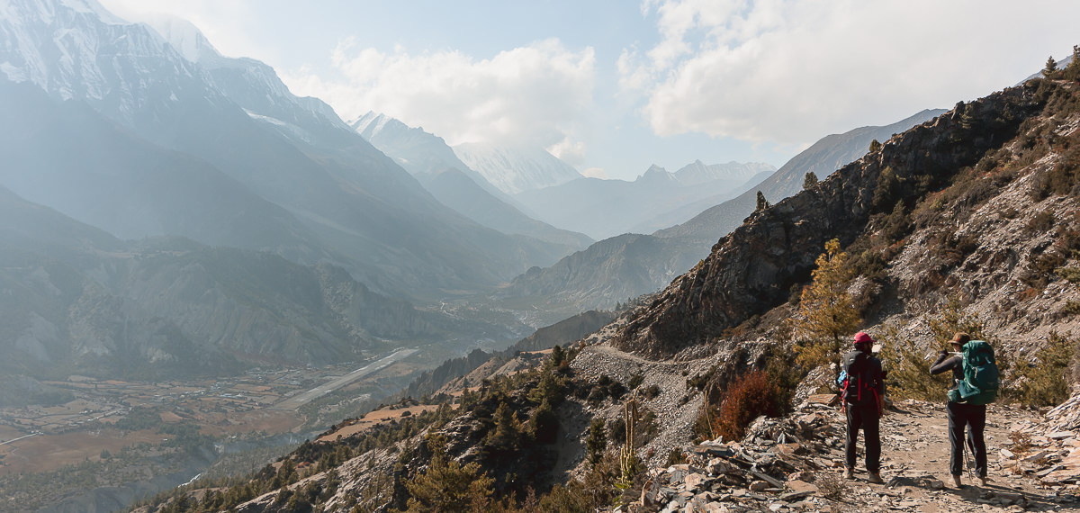 A trekker and guide on the high trail to Ngawal with an expansive view over the Manang Valley
