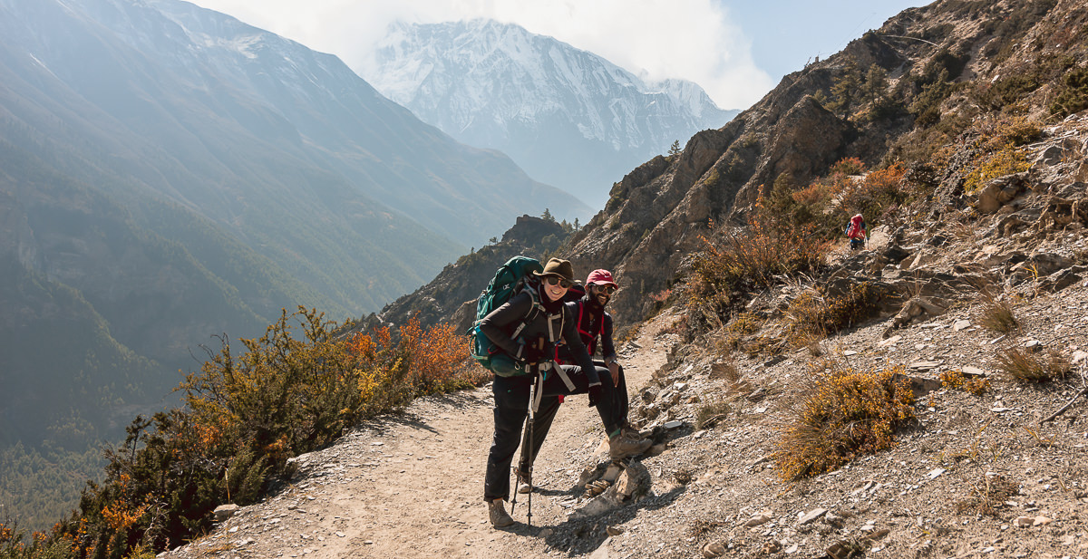 A trekker and guide stand smiling on the sunny trail to Ngawal on the Annapurna Circuit