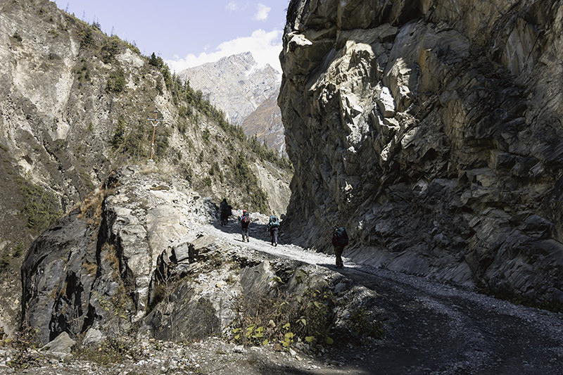 Trekkers walking under a rocky overhang, blasted to make a trail on the Annapurna Circuit trek