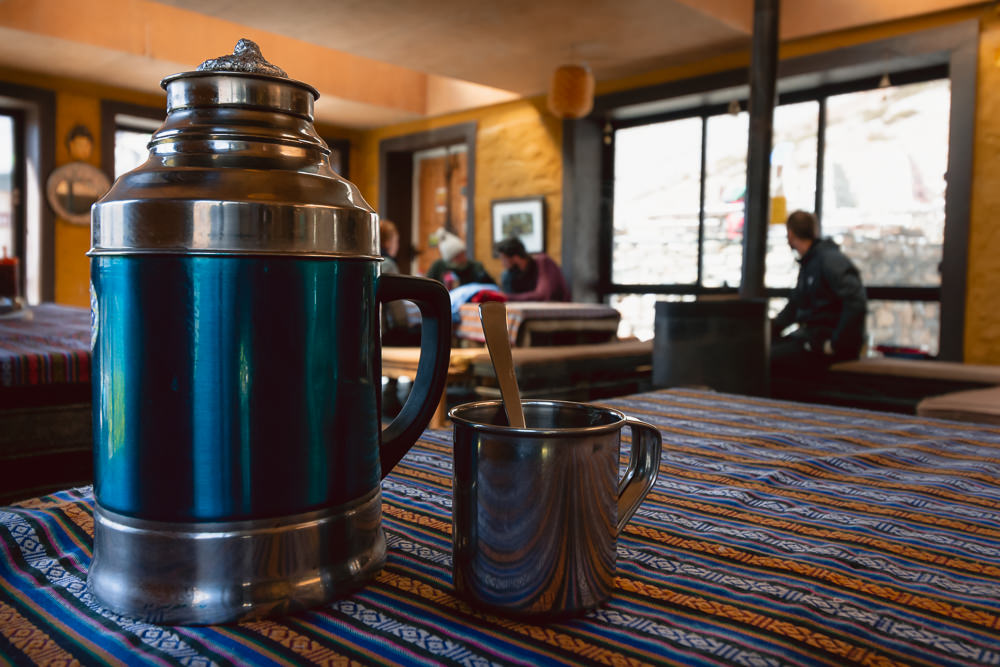 A large blue and silver thermos flask of tea sits alongside a metal mug on a colourful tablecloth in the Windhorse Restaurant at Thorong Phedi on the Annapurna Circuit