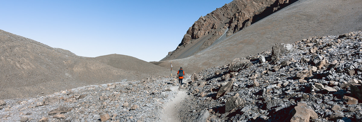 A trekker with a bright red coat hiking the gravel trail towards Thorong La on the Annapurna Circuit
