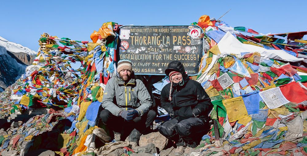 Two trekkers posing at the Thorong La sign surrounded by colourful prayer flags