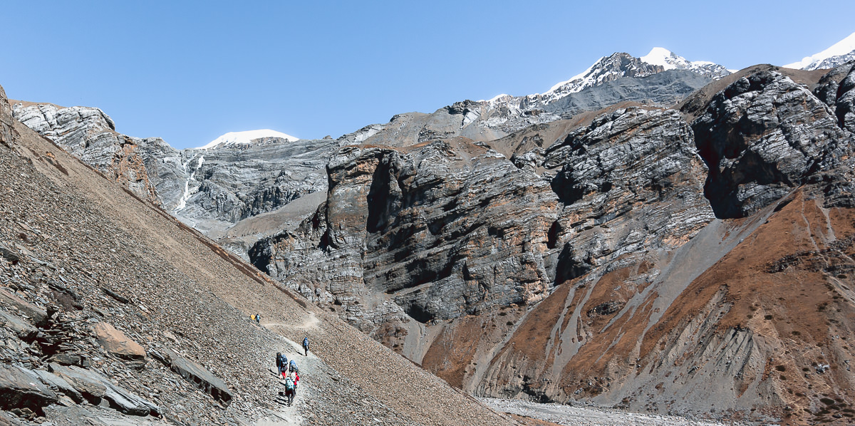 Trekkers crossing a landslide area of loose rocks, surrounded by looming cliffs, just before Thorong Phedi on the Annapurna Circuit