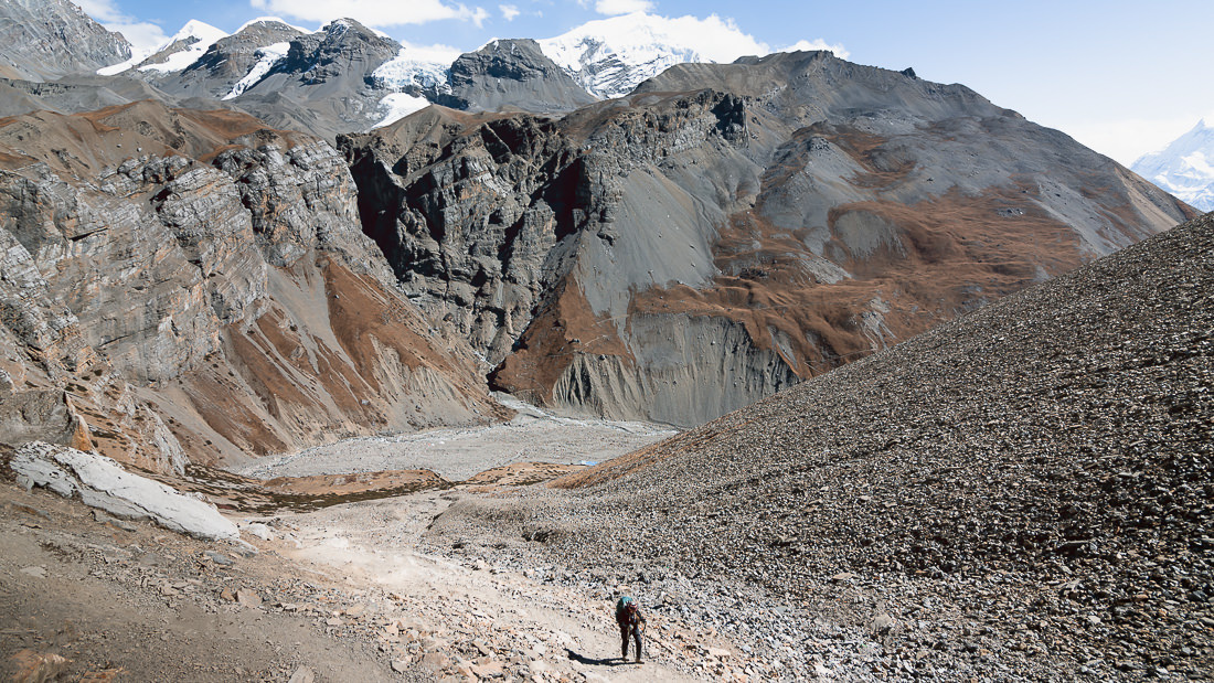 A trekker climbing the rocky slope from Thorong Phedi to Thorong High Camp
