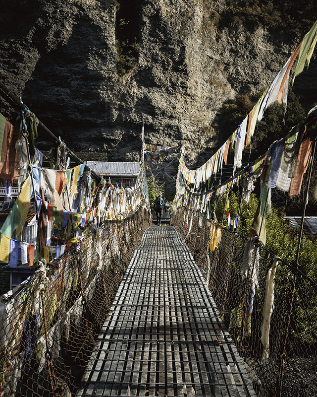 A person crosses a metal footbridge draped with countless prayer flags on the Annapurna Circuit Trek
