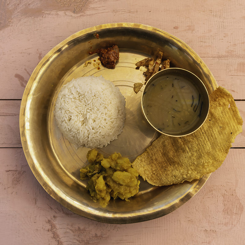 A serving of classic Nepali dish dal bhat on a brass plate, sitting on a peach coloured wooden table