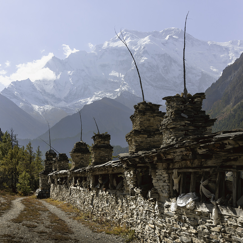 A long Mani Wall stretching out with snow covered mountains of the Annapurna Circuit trek in the background