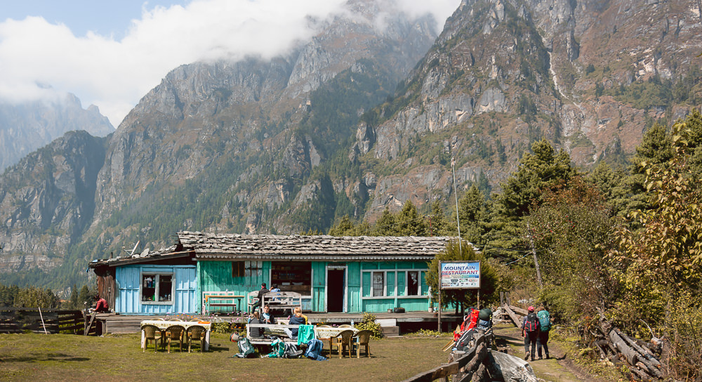 Trekkers sit for lunch in the garden of a teahouse, with cloud topped mountains in the background