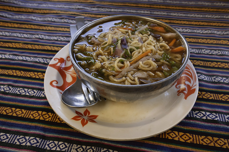 A bowl of veg noodles on a colourful table cloth in an Annapurna Circuit dining room