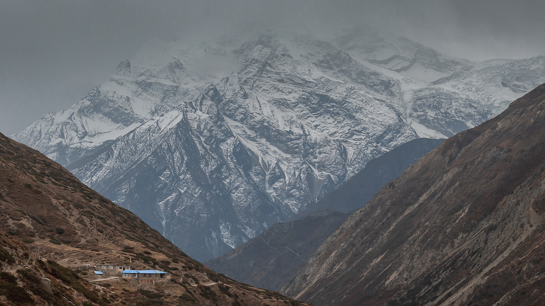 Snowy mountains looming over blue roofed trekking lodges as seen from Yak Kharka on the Annapurna Circuit