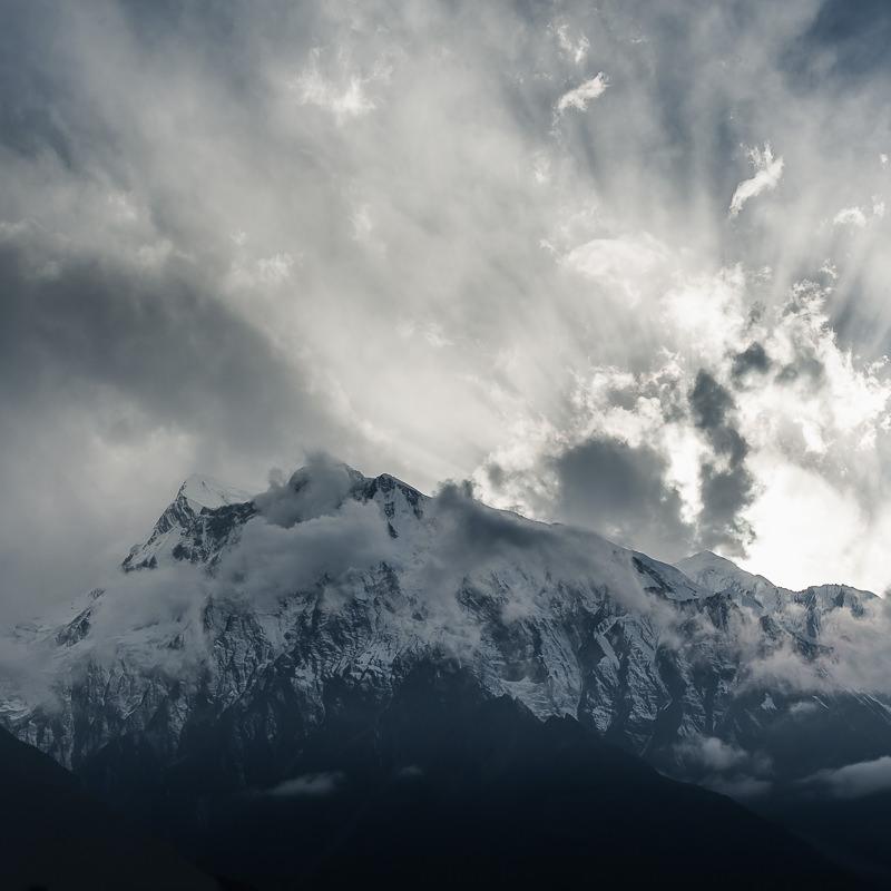 Annapurna III and Gangapurna peaks enshrouded with clouds at sunset