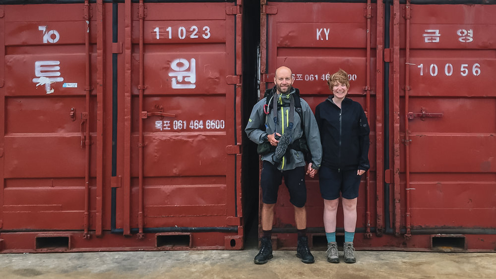 Kim and Del Hogg standing in front of red containers on Olle Trail Route 11 for their (late) third wedding anniversary photo