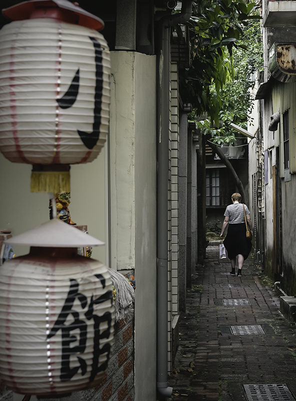 A person wandering a narrow back lane in the Anping District of Tainan