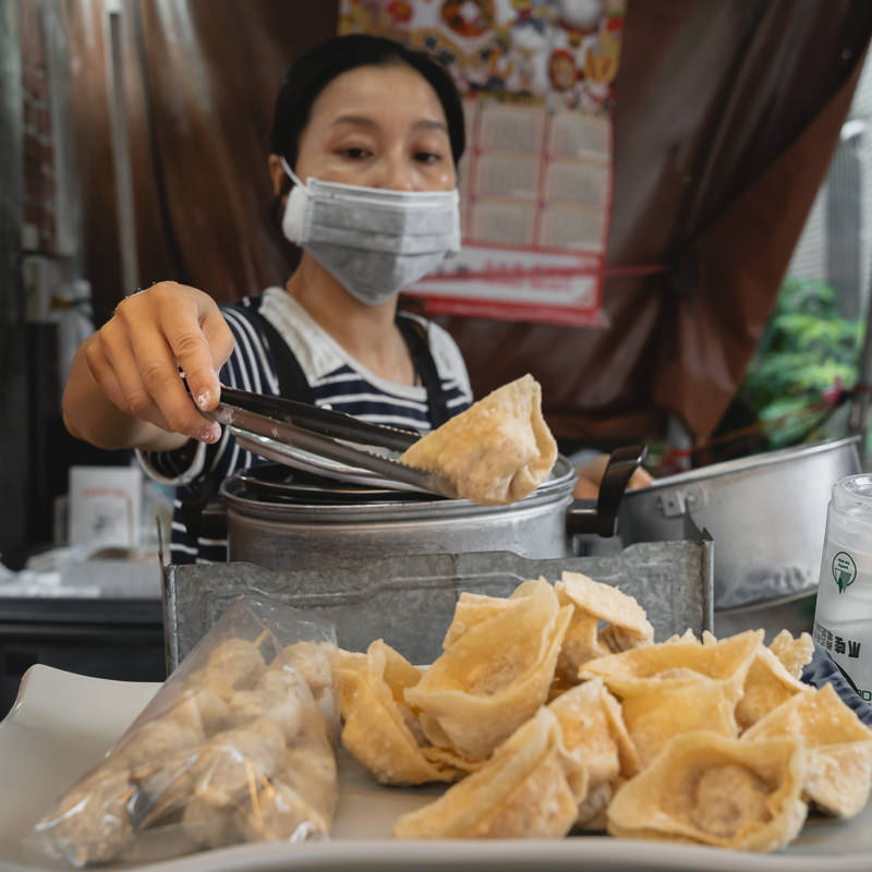A lady in the Anping District of Taiwan selling wontons and coffin bread